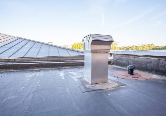 on a high building in the city there is cooling on a flat roof